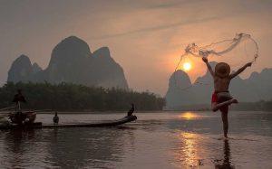 Barco con pájaros cormoranes, la pesca tradicional en el uso de China de los cormoranes capacitados para pescar, Yangshuo, China
