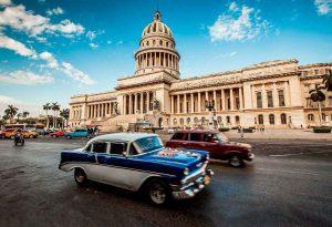 Imágen de la Habana con edificio antiguo y coches pasando por la calle en primer plano