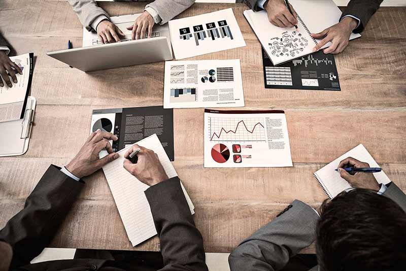 Detalle de manos sobre escritorio trabajando con ordenadores e informes