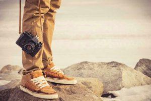 Piernas de hombre con pantalón y zapatillas con cámara fotografica colgado. En la sima de unas montañas.