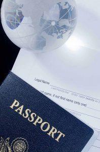 Pasaporte y globo terraquea sobre formulario de visados