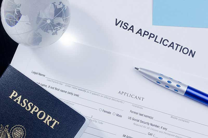 Pasaporte y bolígrafo sobre formilario de visado